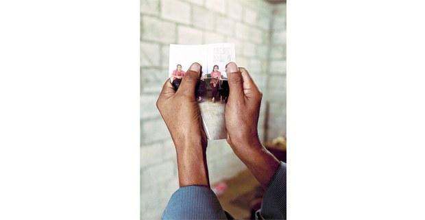Padre muestra la foto de su hija que fue herida por los paramilitares. Foto: Luis Enrique Aguilar Pereda.